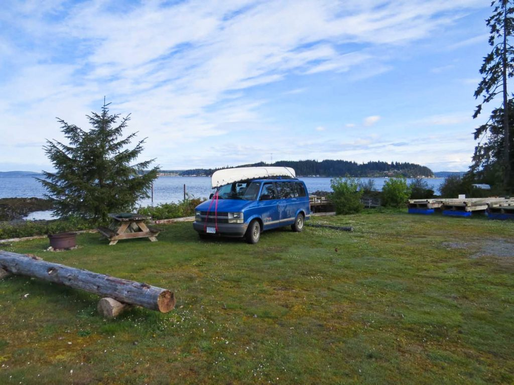 Blue van is parked in a campsite with ocean views at Alder Bay campground