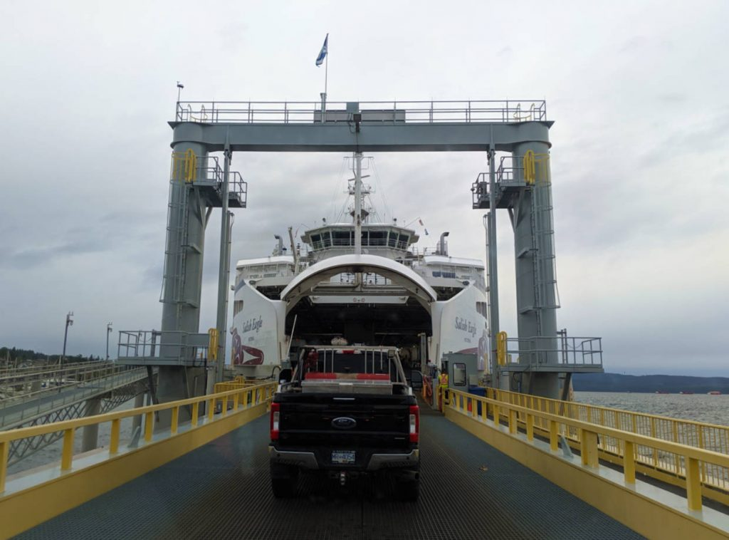 Following a truck onto a ferry, with yellow barriers and peek through ocean views
