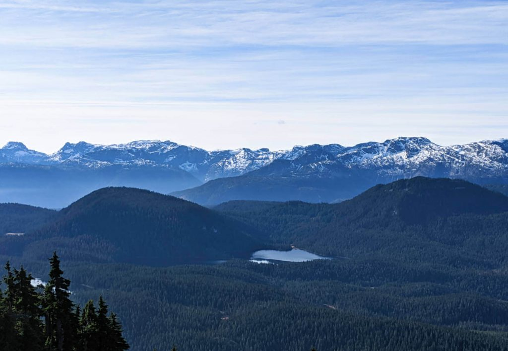 Looking down to Strathcona Provincial Park, with forest, lakes and snow capped mountains