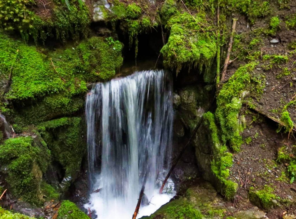Wide waterfall falling into mossy chasm