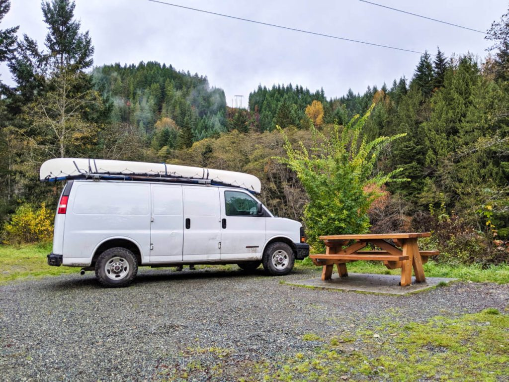 White van parked up next to picnic table with misty forest behind