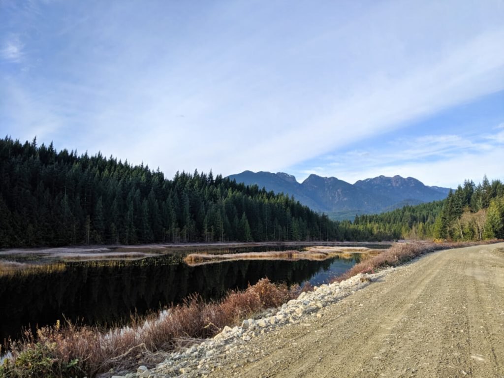 Gravel road next to pond/lake area, with mountain in background