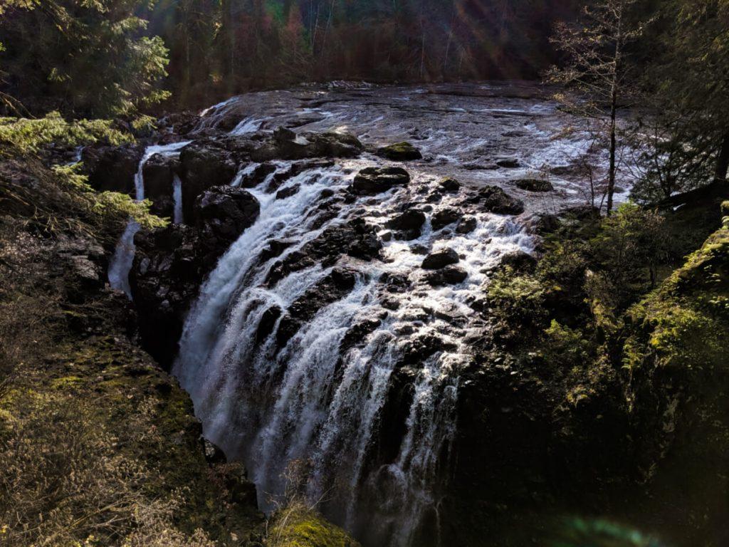 Wide multi-stream waterfall falling into deep canyon below