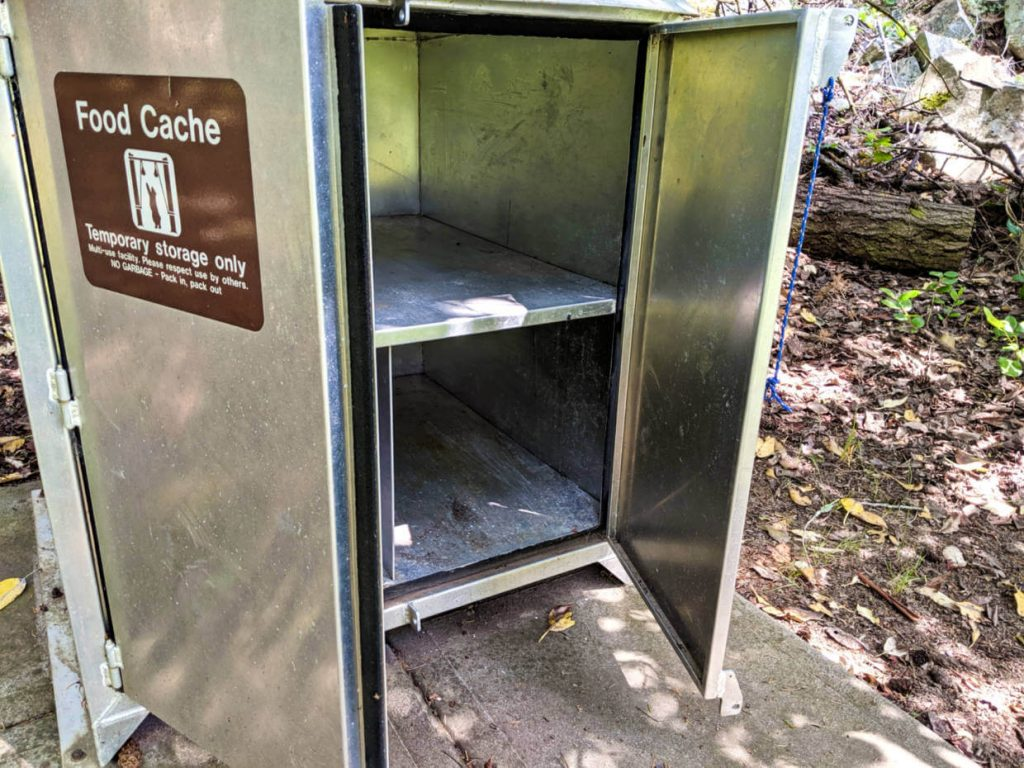 Looking inside a metal food cache with shelves and open doors