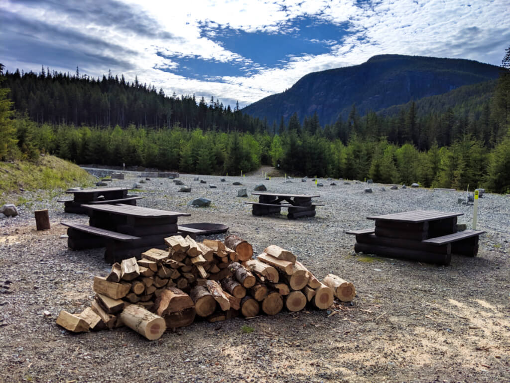 Open campground with many picnic tables and large pile of chopped wood, in elevated area