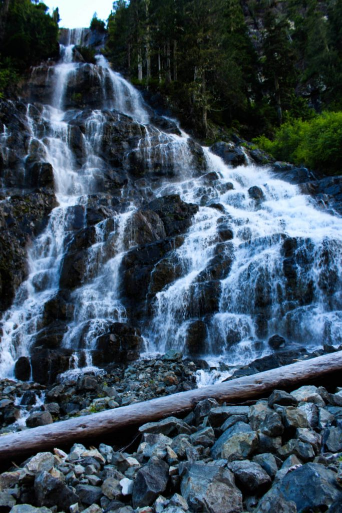 A tall waterfall cascades towards camera, with multiple drops