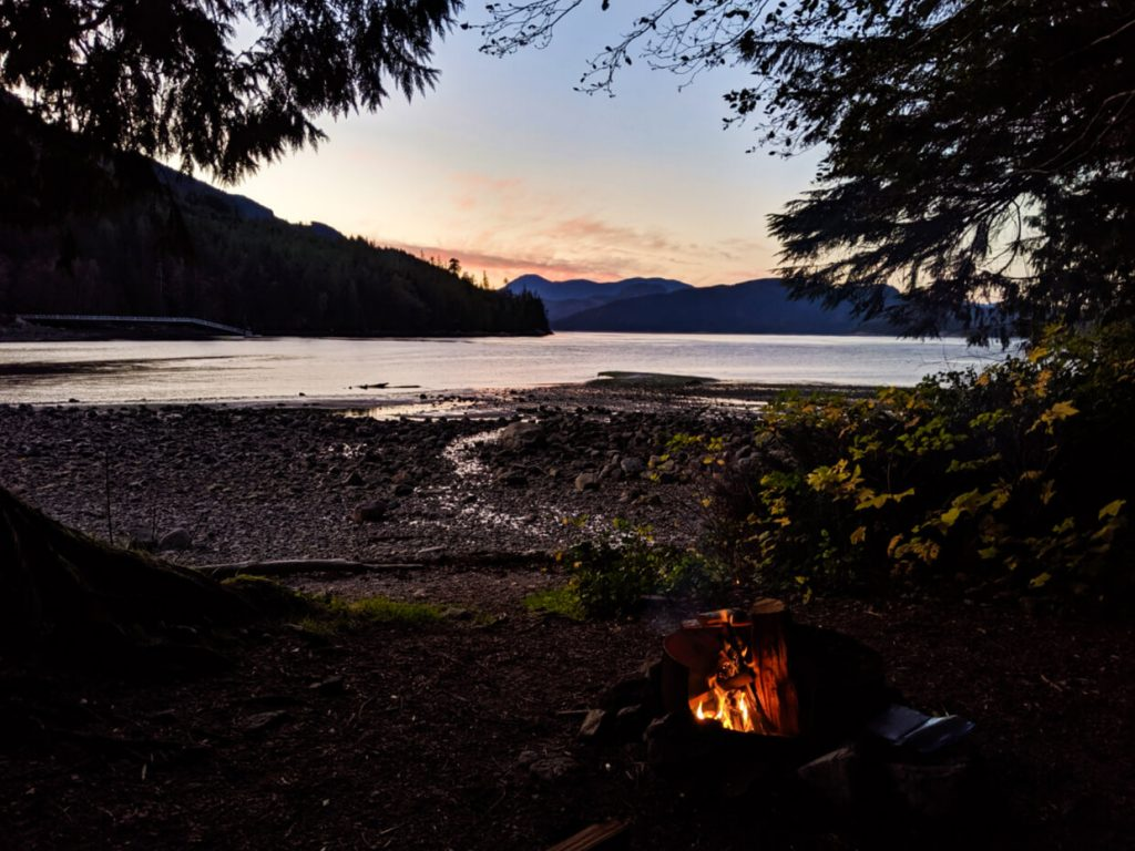 Lit campfire in front of coastal scenery