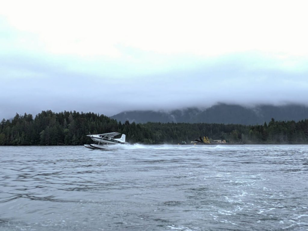 Seaplane taking off in Tofino harbour with backdrop of forest and misty mountains