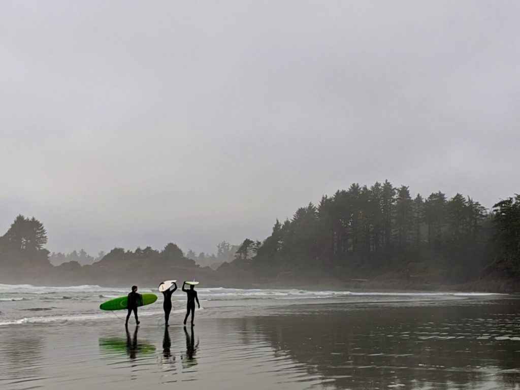 Three surfers walk with their boards away from the camera, on a sandy beach near Tofino