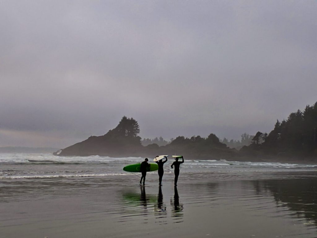 Surfers waling along wet beach in Tofino with boards on hea