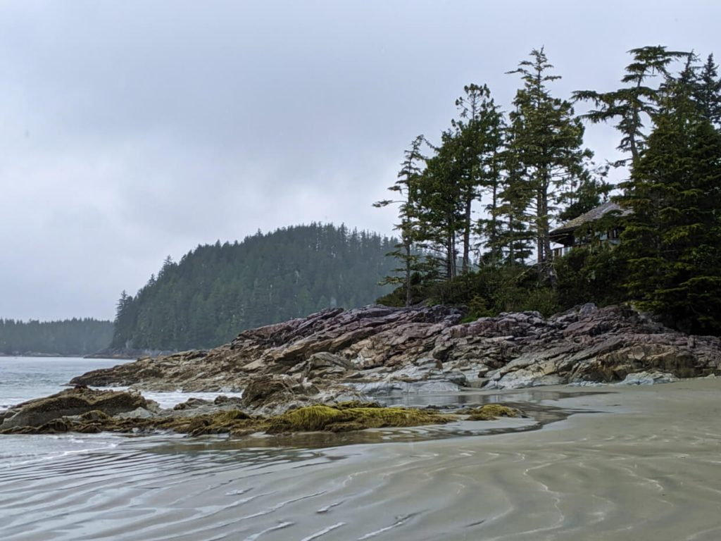 Rocky headland with trees, on sandy beach in Tofino
