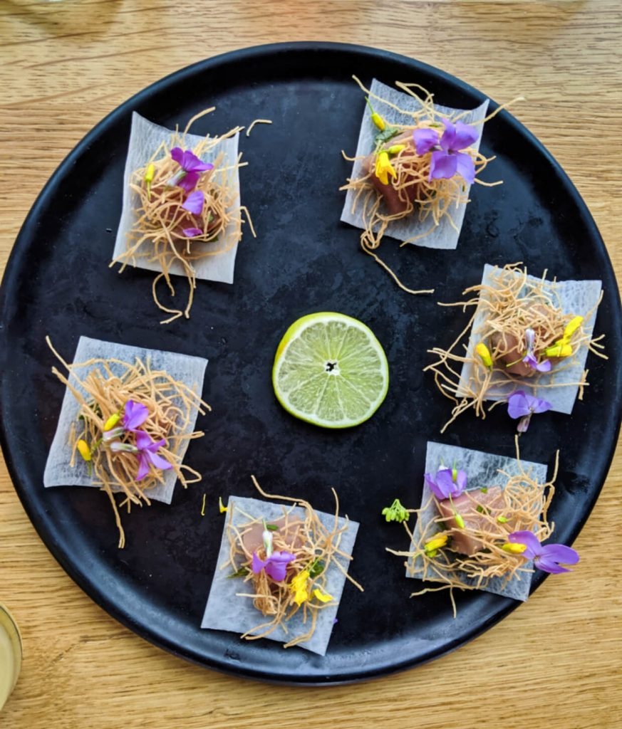 Overhead shot of black plate with small pieces of tuna, dressed with flowers and noodles