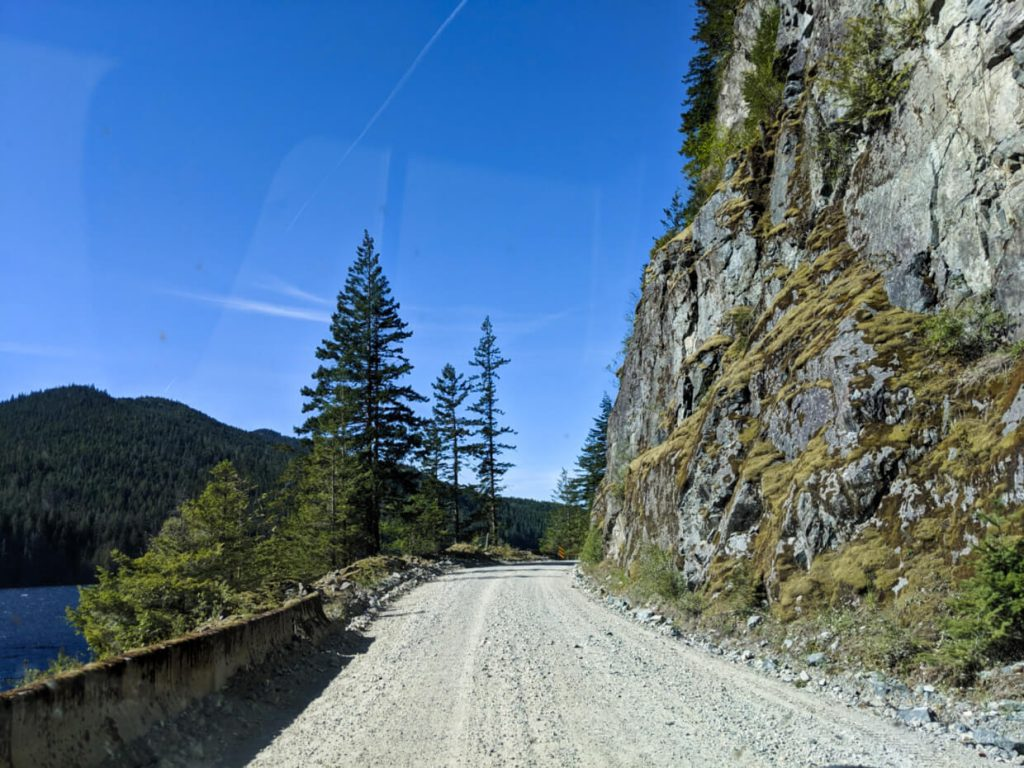 Windshield view of gravel road on Vancouver Island with mossy cliff on right and lake (with barrier) on left